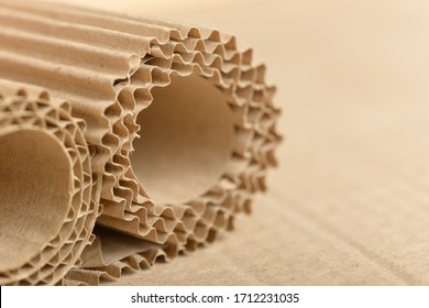 Carton or cardboard packing material. Texture of corrugated paper sheets made from cellulose. Supplies for creating boxes and packaging. Pasteboard background. Natural brown cardboard surface.