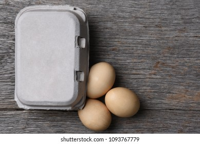 A Carton of fresh eggs with three on the rustic wood table. Horizontal with copy space.