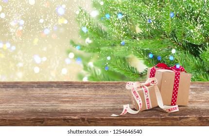 Carton gift boxes on wooden table, border with christmas tree in background
