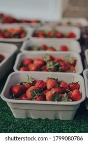 Carton punnets of fresh strawberries on display on a local market stall in the Cotswolds, UK.
