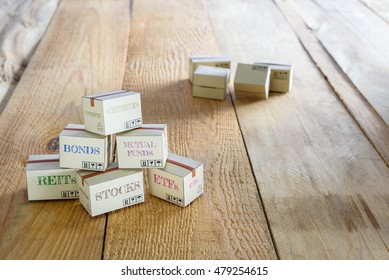 Cartons of financial investment products put on the floor i.e REITs, stocks, ETFs, bonds, mutual funds, commodities. A concept of portfolio management with risk diversification for optimal returns.