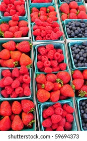 Cartons of fresh strawberries, blueberries and raspberries at a farmers market.