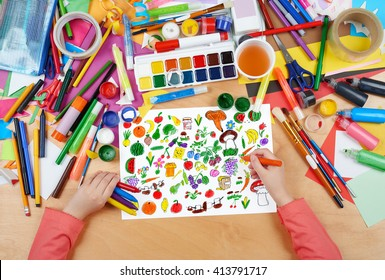 cartoon food collection, fruit and vegetables child drawing, top view hands with pencil painting picture on paper, artwork workplace