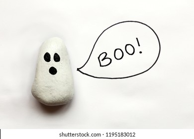 A cartoon painted Halloween Ghost rock is isolated on a white background with a speech bubble that says boo.