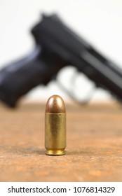 cartridge close up, pistol shape in background