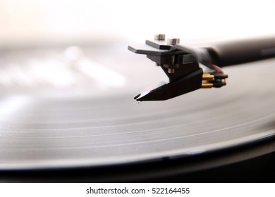 Cartridge of a modern high quality turntable record player about to be lowered onto a vinyl analogue music LP