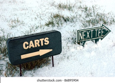 carts and next tee sign on a snow covered links golf course in ireland in snowy winter weather