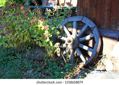 cartwheel, old, wooden, stands near the wall of the house.