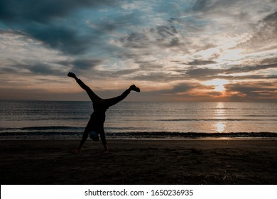 cartwheel on a beach man evening background acrobatic shadow gymnastic fitness