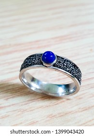 carve sliver ring with blue stone on the wood