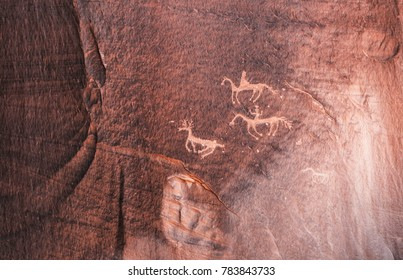 Carved Anasazi petroglyphs representing two horse riders hunting an animal related to deer - Canyon de Chelly National Monument - Arizona.