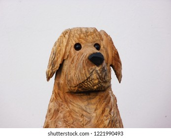 Carved dog head made of wood with white background. With black eyes and nose.