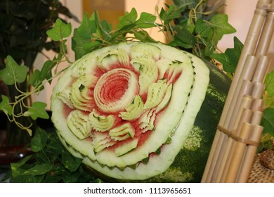 Carved fruit of watermelon to flower form and green leaves put beside Lao reed mouthorgan.