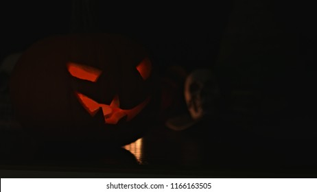 Carved Halloween pumpkin lights inside with flame and skuls around on a black background.