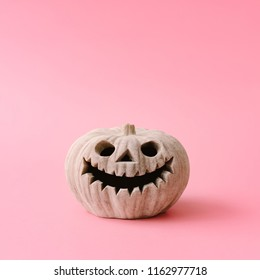 Carved Halloween pumpkin on pastel pink background. Creative Halloween minimal concept.
