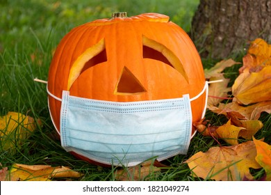 Carved Halloween pumpkin with sad eyes wearing mask on the grass with leaves, no party during Covid or Coronavirus outbreak, events and parties canceled to prevent the risk of spreading the virus
