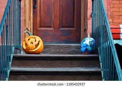 Carved Halloween pumpkins or jack o'lantern on the doorstep in Brooklyn, New York City