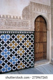Carved islamic wall decoration filled with colourful tiles, Alhambra, Granada, Spain.
