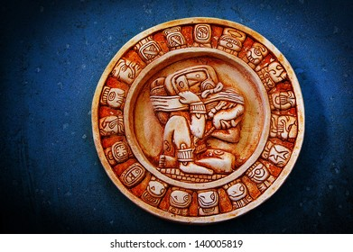A carved Mayan calendar on textured background