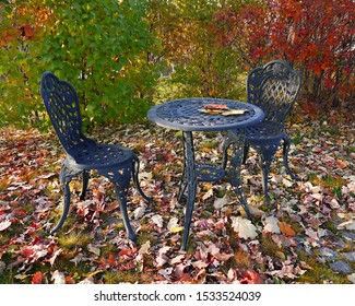 Carved metal table and chairs stand outside surrounded by autumn scenery. Relaxing