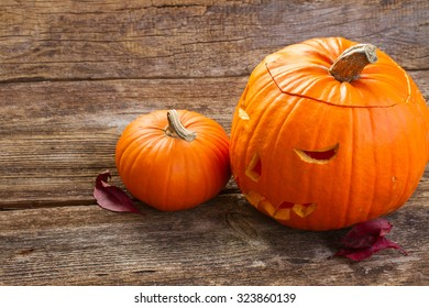 Carved orange scary halloween pumpkin on aged wooden table