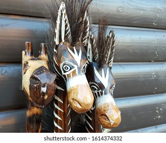 Carved Painted Wooden Animal Heads against background of Painted Slatted Wood