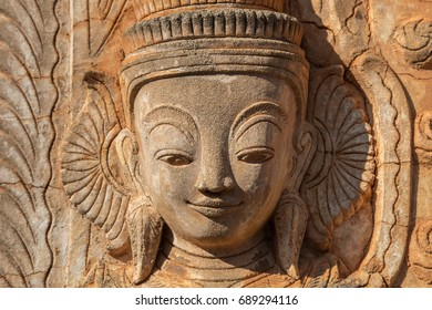 Carved portrait of a beautiful smiling woman on a wall of ancient ruined Buddhist temple in Indein, Inle lake area, Myanmar