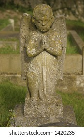 A carved praying angel headstone covered in moss