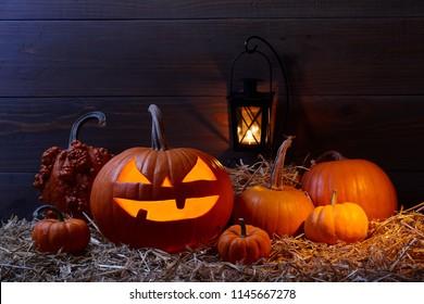 Carved pumpkin jack lantern and pumpkins in dark barn, Halloween holiday celebration concept