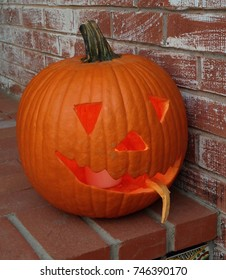 Carved pumpkin on a doorstep in front of a brick wall