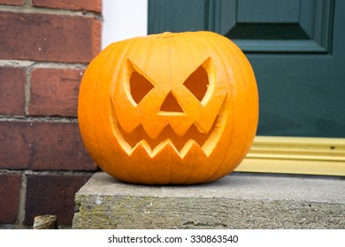 Carved pumpkin on a doorstep, isolated.