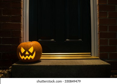 Carved pumpkin on a doorstep at night.
