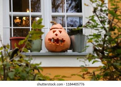 Carved pumpkin on a window till, outdoor Halloween decoration. Selective focus.