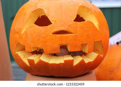 Carved pumpkin with a scary face in daylight