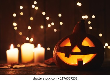 Carved pumpkin with scary face as symbol of Halloween and candles on sparkling background. Halloween decoration concept