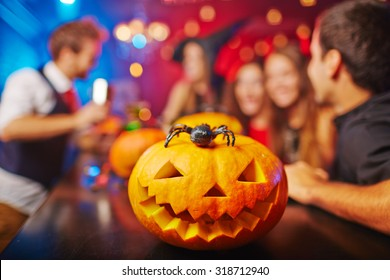 Carved pumpkin and spider on background of group of friends celebrating Halloween in bar