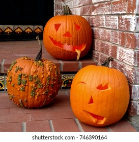 Carved pumpkins on a doorstep in front of a brick wall