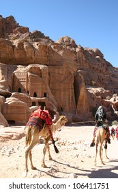 At the carved rock city of Petra in Jordan, a bedouin walks by a home of rock with his camel.