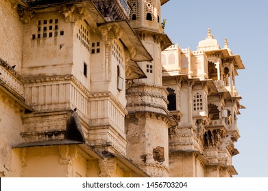 Carved sandstone exterior walls of the udaipur palace with arches, balcony and windows. The majestic city palace is a museum that is a must visit for tourists for it's historical significance and