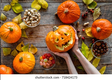 Carved smiling halloween pumpkin head among pumpkins on wooden background top view