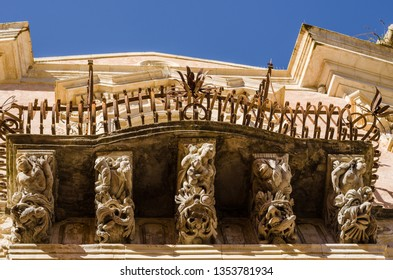 Carved stone balcony supports in baroque town of Ragusa, Sicily, Italy.