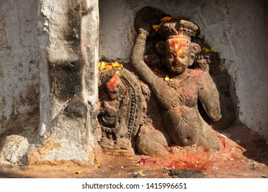 Carved stone figures with colorful offerings of flowers and powders at Swayambhunath Buddhist temple, Kathmandu, Kathmandu Valley, Nepal
