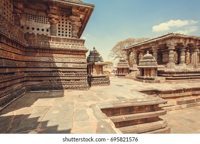 Carved stone walls of beautiful temple buildings of Halebidu, with columns and reliefs of the 12th century Hoysaleshwara temple, India