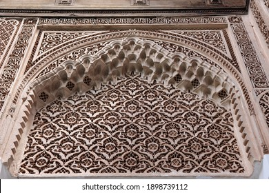Carved wooden art ornaments with traditional details in moroccan oriental design, arabic decoration at historic archway wall in old royal Bahia Palace in arabian medina of Marrakech, Morocco, Africa.