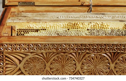In a carved wooden box are a honeycomb with honey. Sold at the fair.