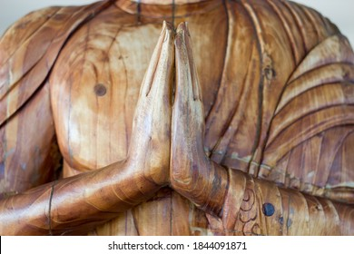 Carved wooden buddha hand Namaste Made Red Wood.  Dhamma of life, Religion concept.