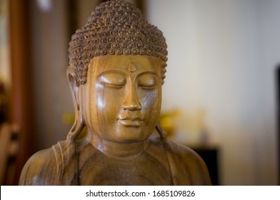 carved wooden Buddha statue in soft light