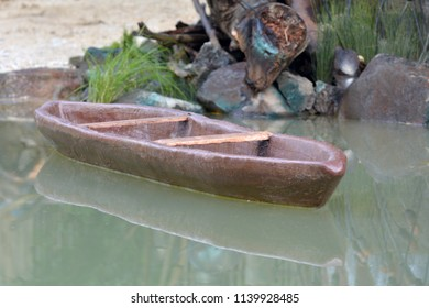 A carved wooden canoe on a calm body of water. Copy space