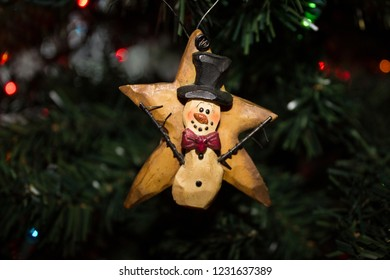 Carved Wooden Christmas Ornament of a Snowman on a Star hanging on an evergreen tree