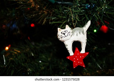 Carved Wooden Christmas Ornament of a White Kitty Cat hanging on a Christmas Tree